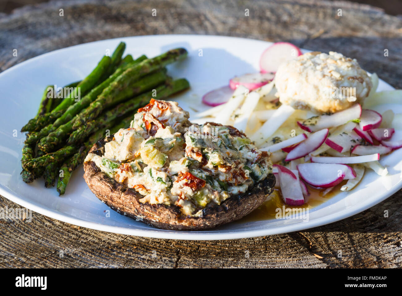 close up of a grilled stuffed mushroom served with charred asparagus and a fennel and radish salad Stock Photo