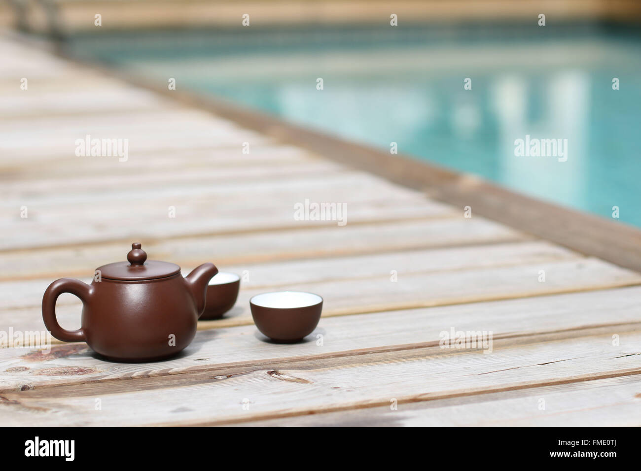 Chinese Tea pot and tea cup by the swimming pool - Stock Image