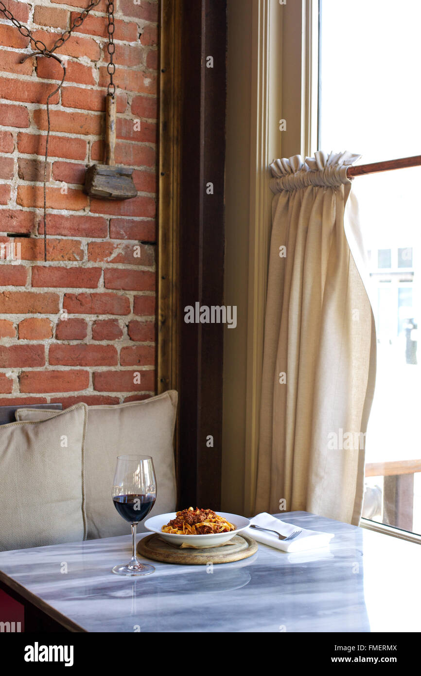 A plate of spaghetti and a glass of red wine for one sit on a table by the window. - Stock Image