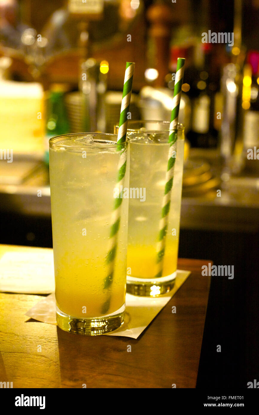 Two lemonades with striped straws sit on a bar top. - Stock Image