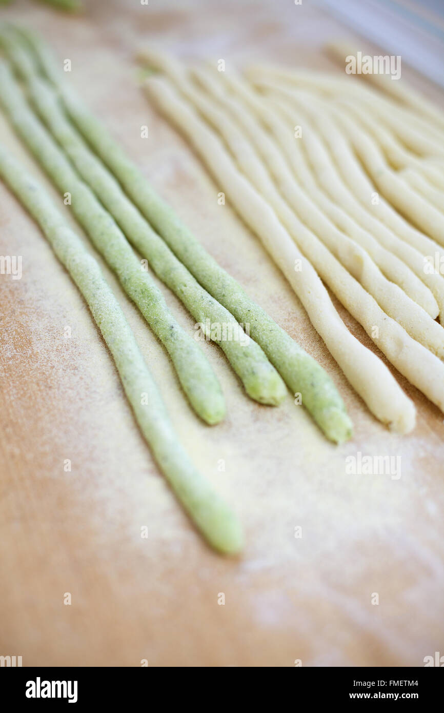 Round strips of green and white pasta dough on a wooden surface dusted with semolina flour. - Stock Image