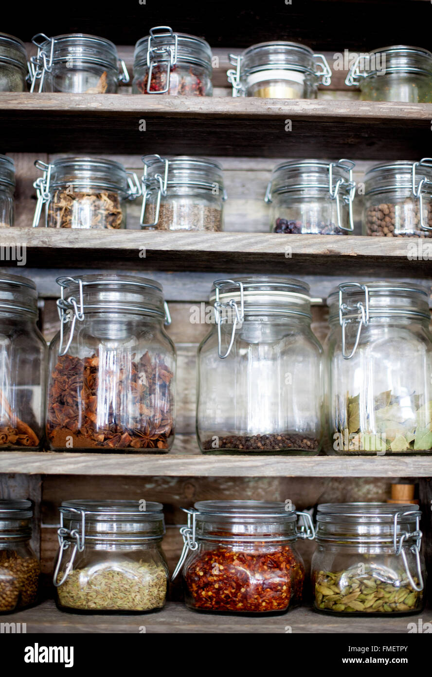 Spice jars of various sizes on a wooden shelf. - Stock Image