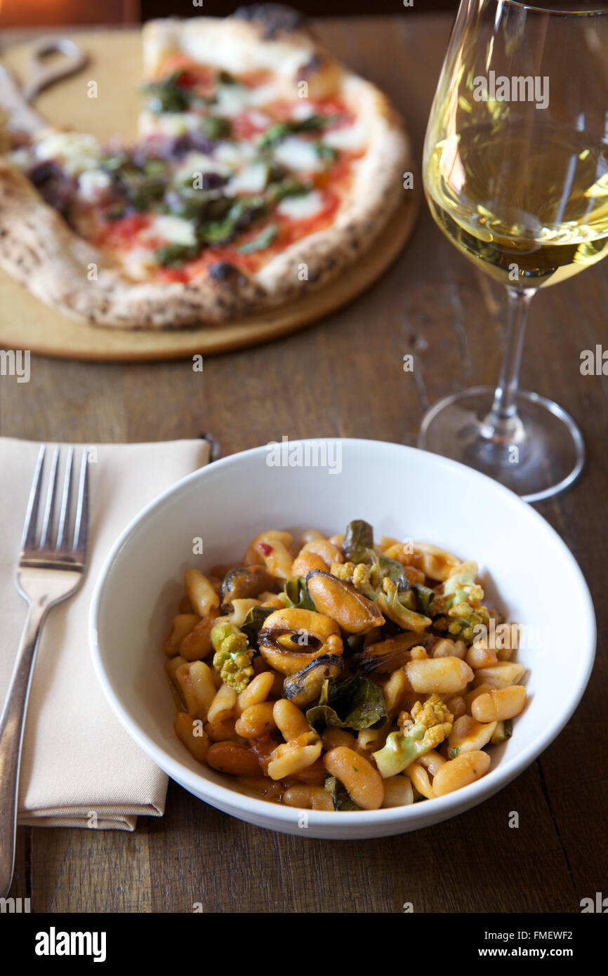 A bowl of white bean, romanesco and mussels soup with white wine and a pizza on the table behind it. - Stock Image