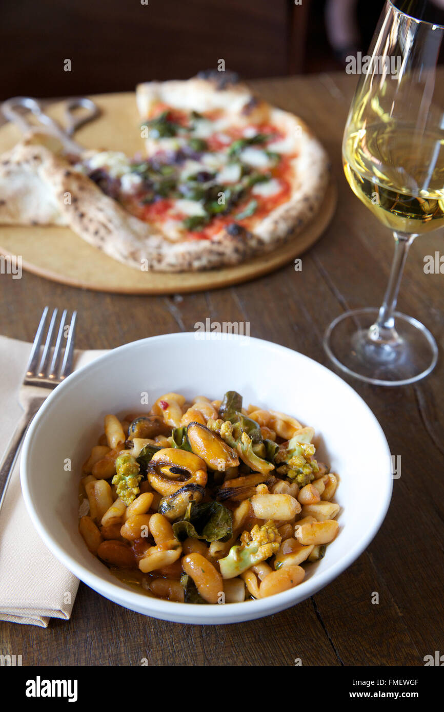 A bowl of white bean, romanesco and mussels soup with white wine and a pizza on the table behind it. Stock Photo