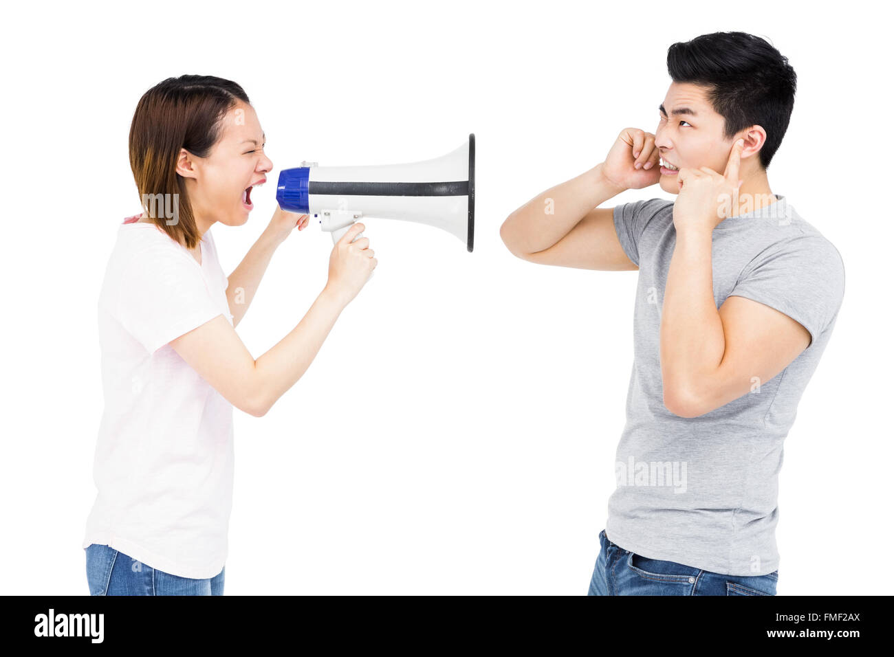 Angry woman shouting at young man on horn loudspeaker - Stock Image