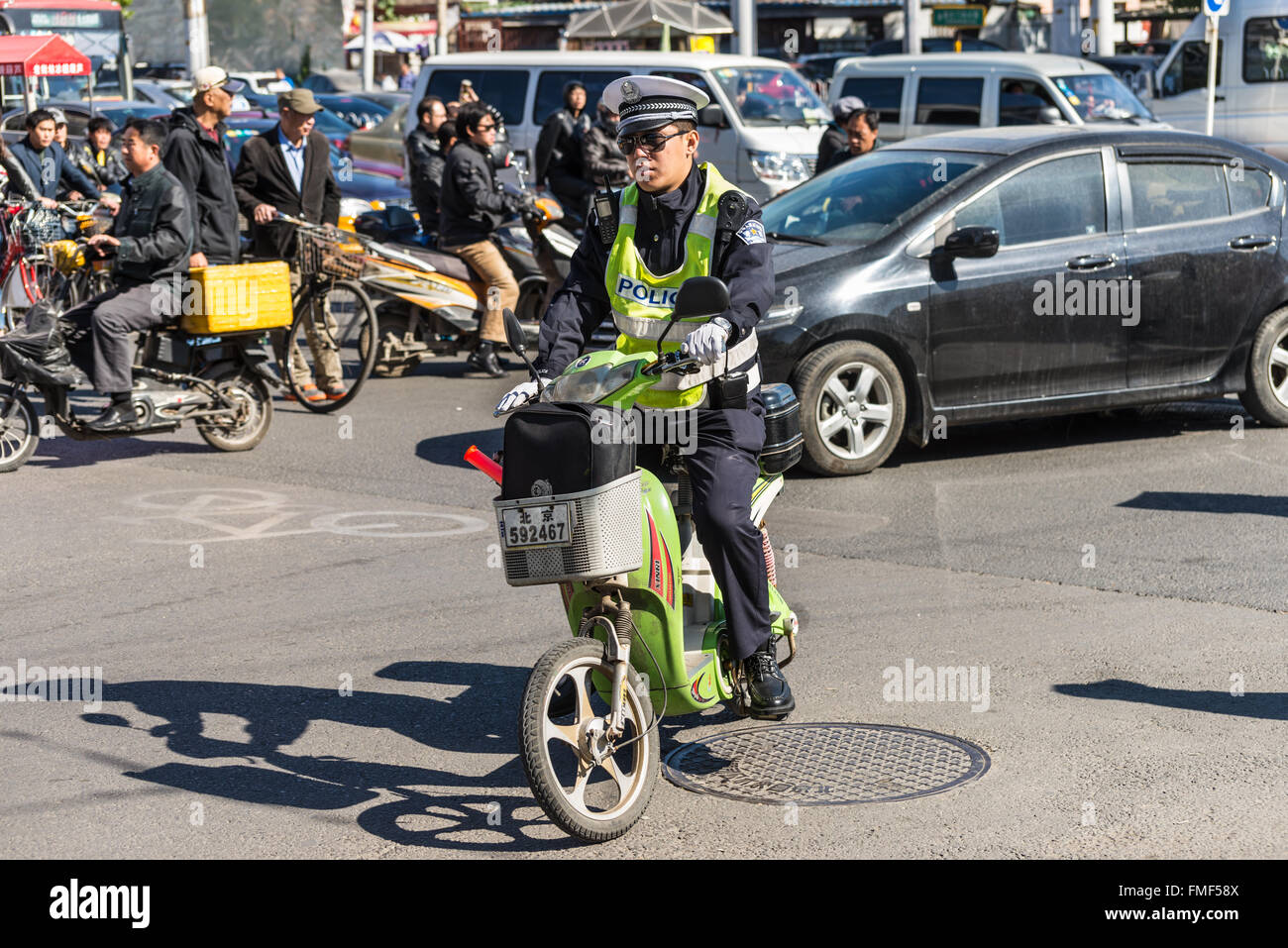 Chinese policeman patrol on motor scooters on a busy street in Beijing, China. - Stock Image