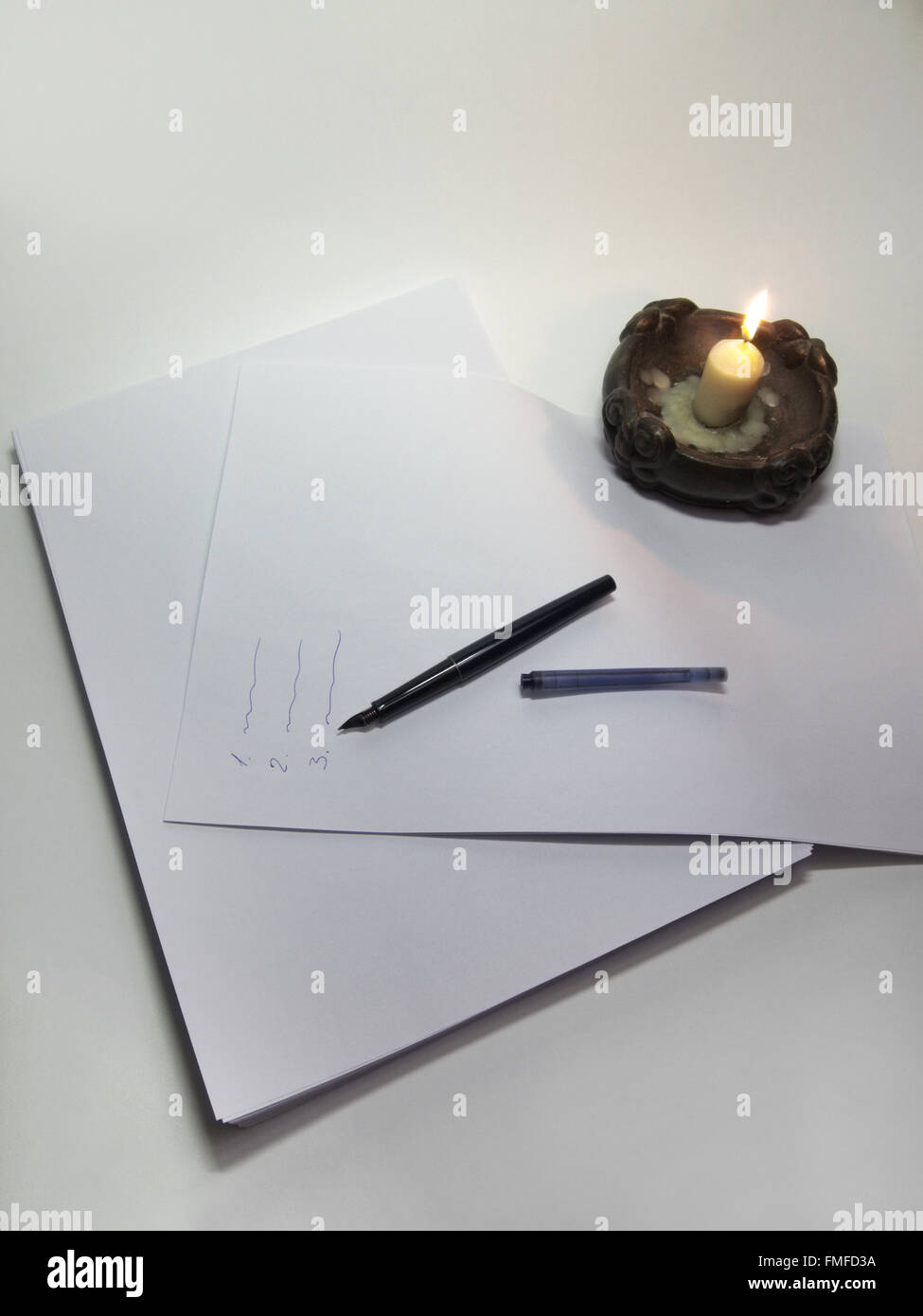 The candle, dismantled fountain pen on the stack of paper. inscriptions list - Stock Image
