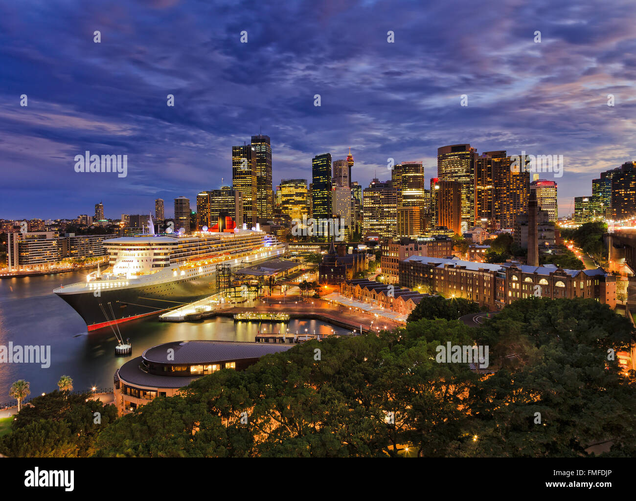 bright lights of SYdney city CBD at sunset as viewed from Harbour Bridge pylon towards Circular quay with docked - Stock Image