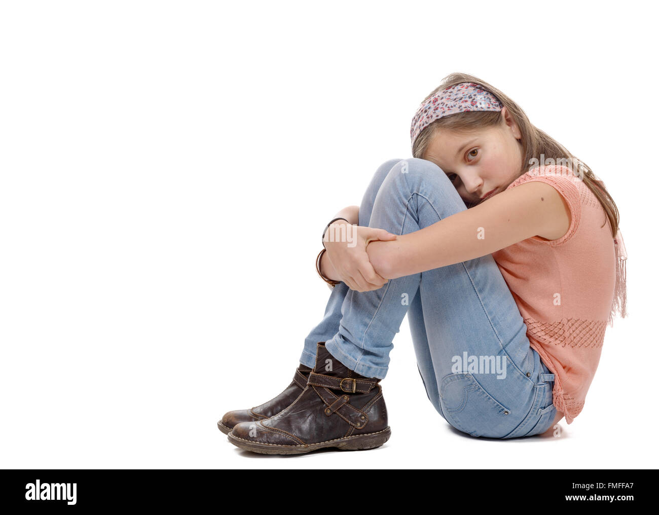 a preteen girl sad  is sitting on the floor - Stock Image