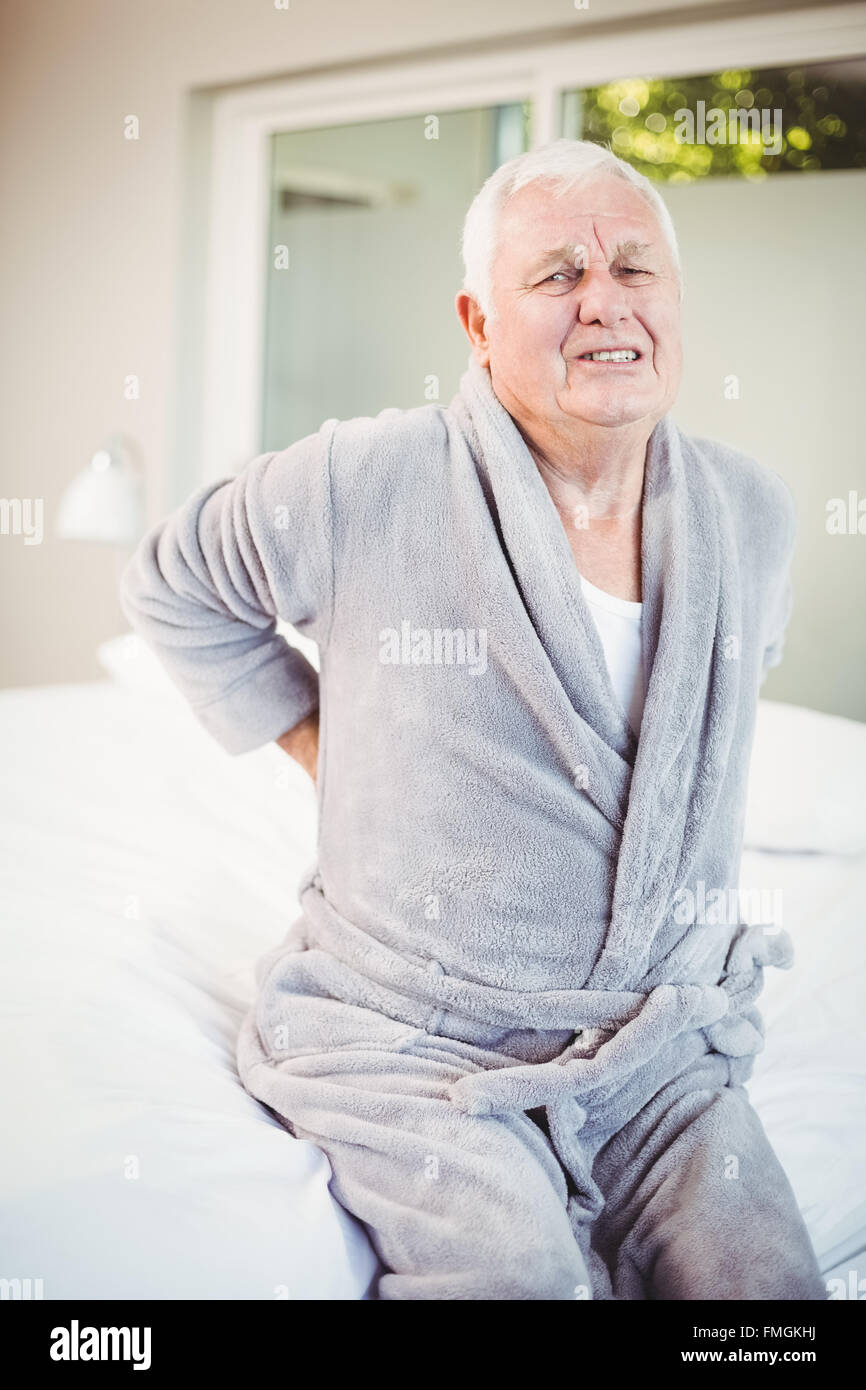 Portrait of man grimacing from back pain - Stock Image