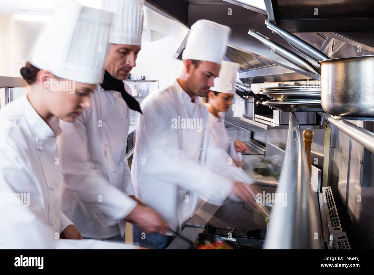 Chefs preparing food in the kitchen - Stock Image
