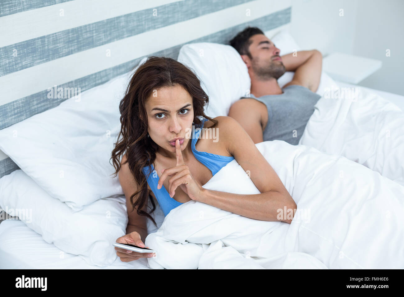 Portrait of woman with finger on lips besides husband sleeping on bed - Stock Image