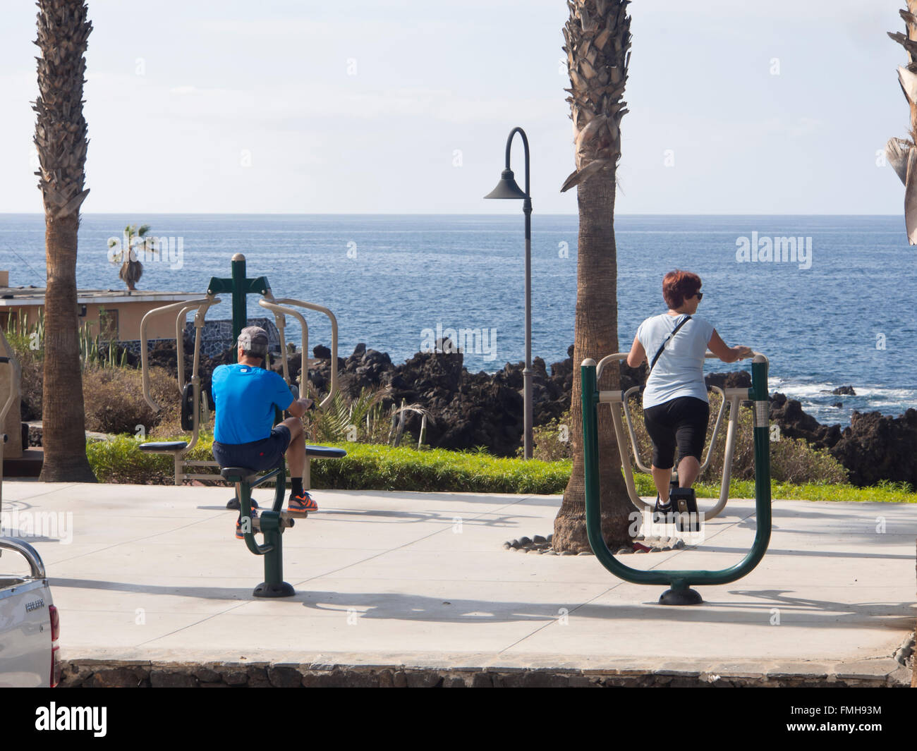 Outdoors exercise apparatus in use on the coastal promenade in Playa San Juan, Tenerife, Canary Islands Spain, active Stock Photo