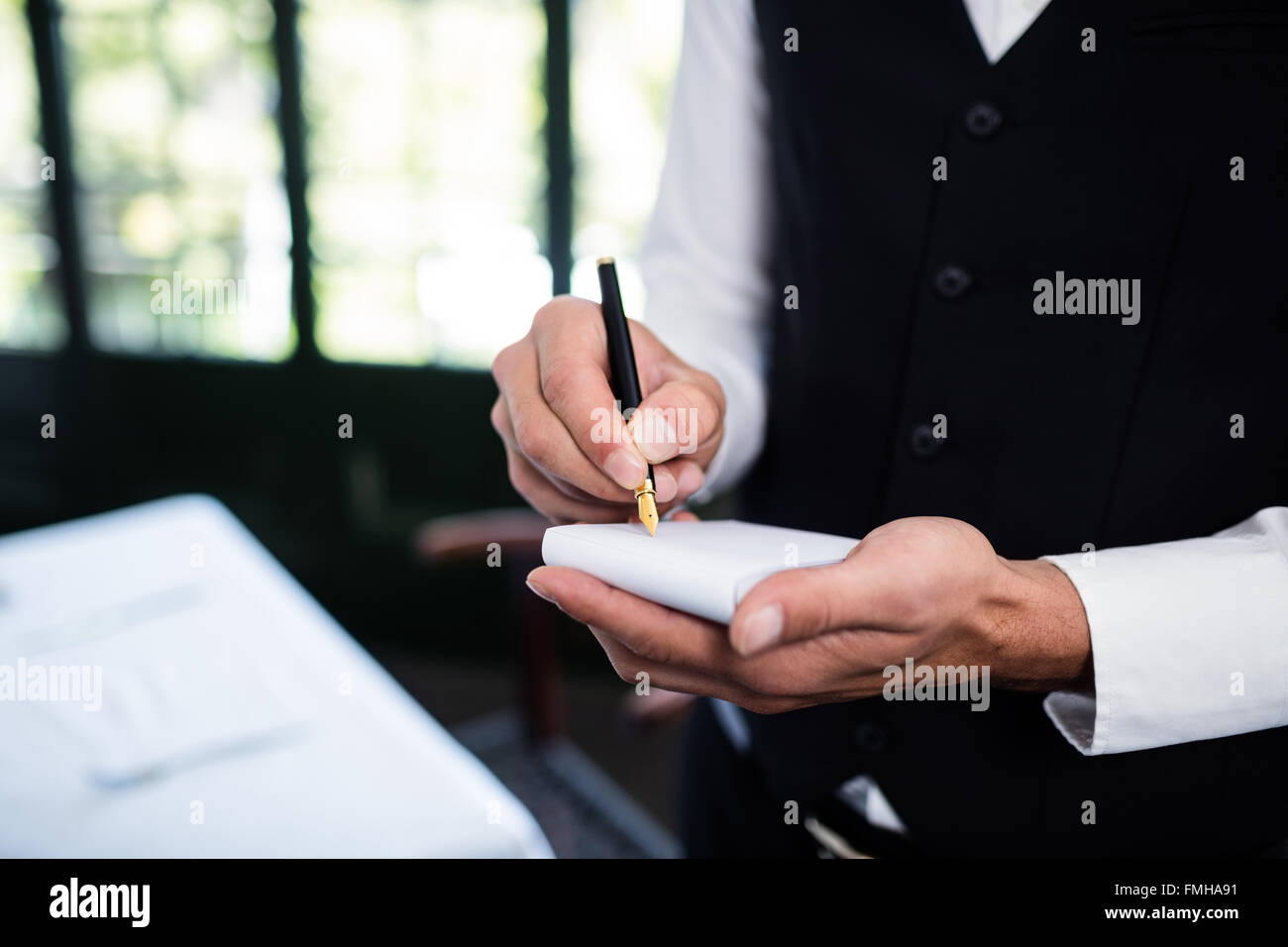 Close-up of waiter taking an order wearing a waistcoat - Stock Image