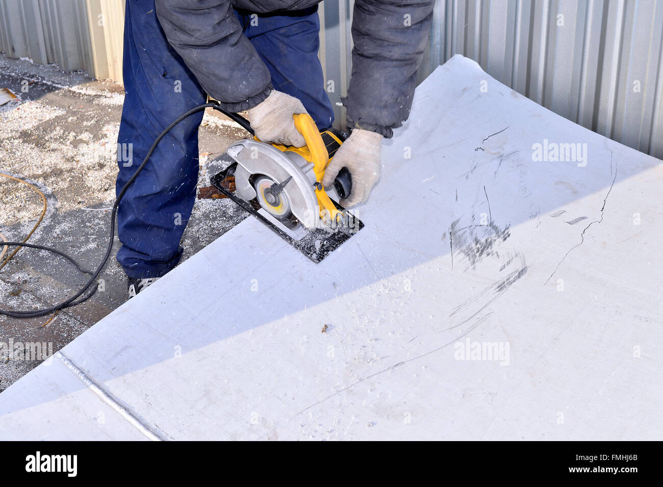 Electric hand tool in the hands of the worker, cutting sheet metal. - Stock Image