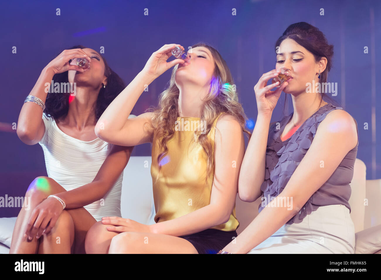 Pretty girls drinking alcohol - Stock Image