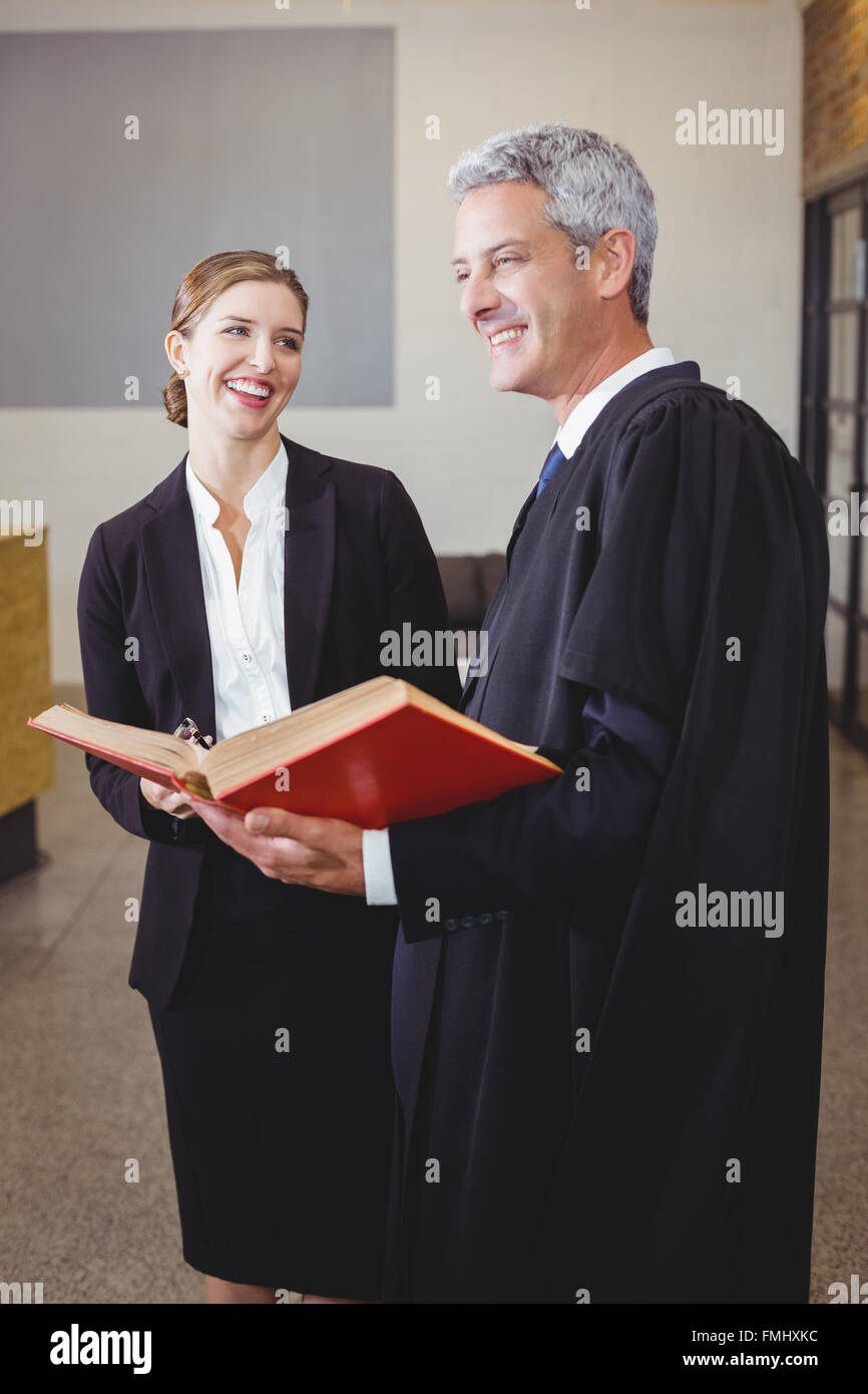 Male lawyer with book standing by female colleague - Stock Image
