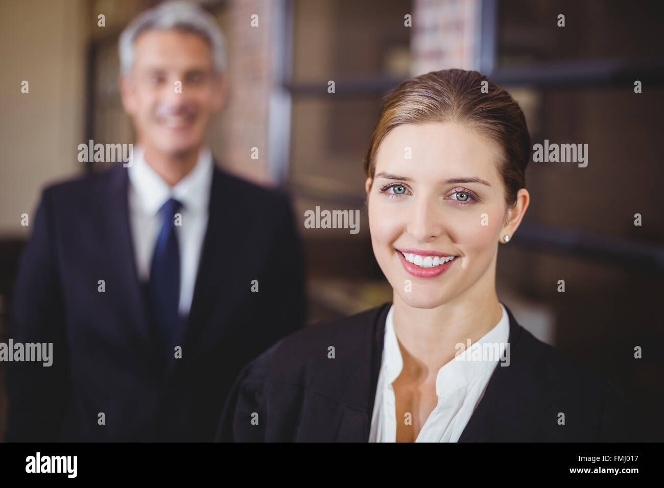 Female lawyer smiling while male colleague in background - Stock Image
