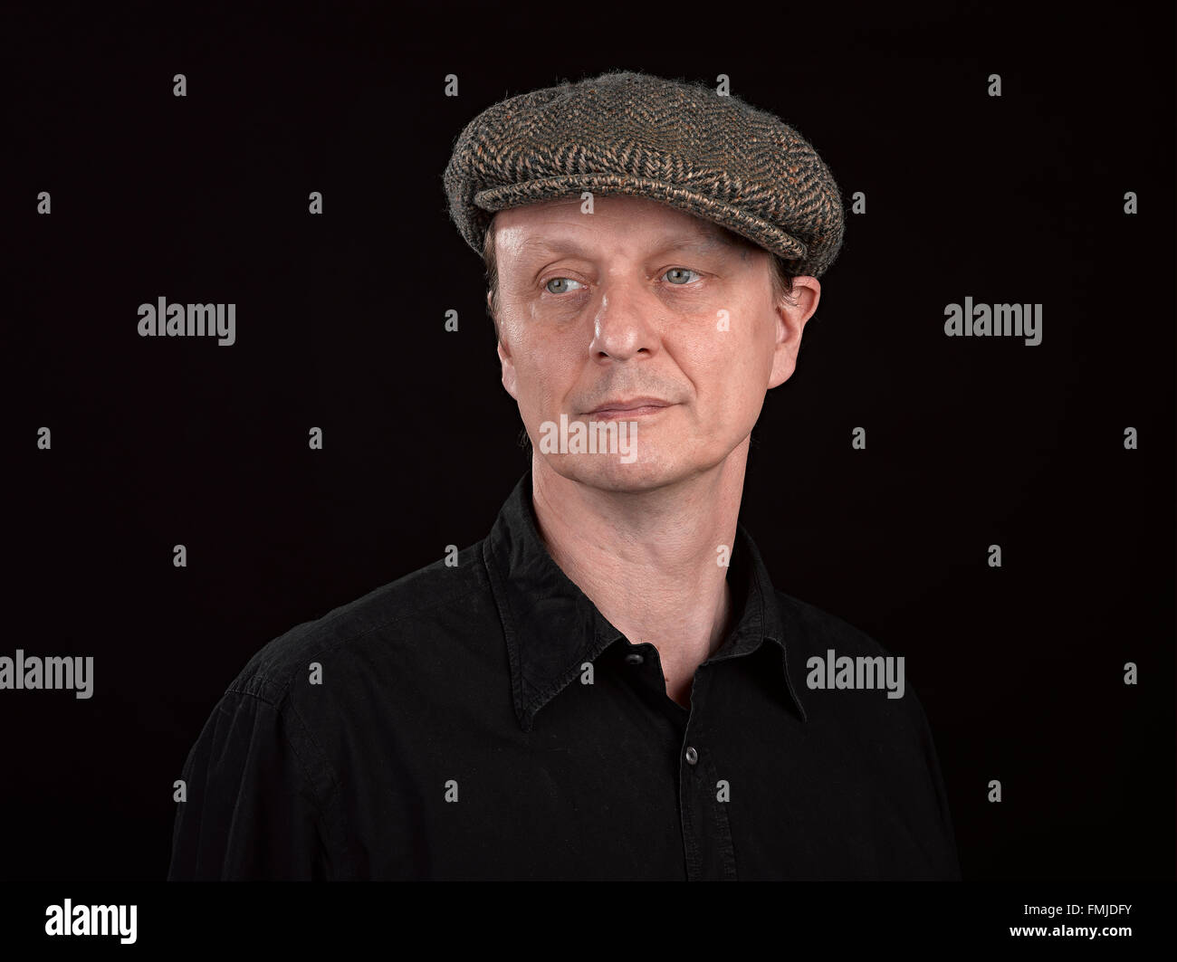 A male model wearing a patterned side hat on black background - Stock Image
