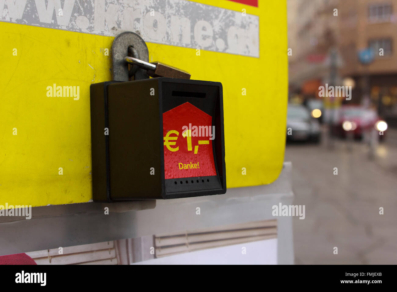 Symbol of Euro currency on a locked contribution box of newspaper selling stand in Vienna, Austria. - Stock Image