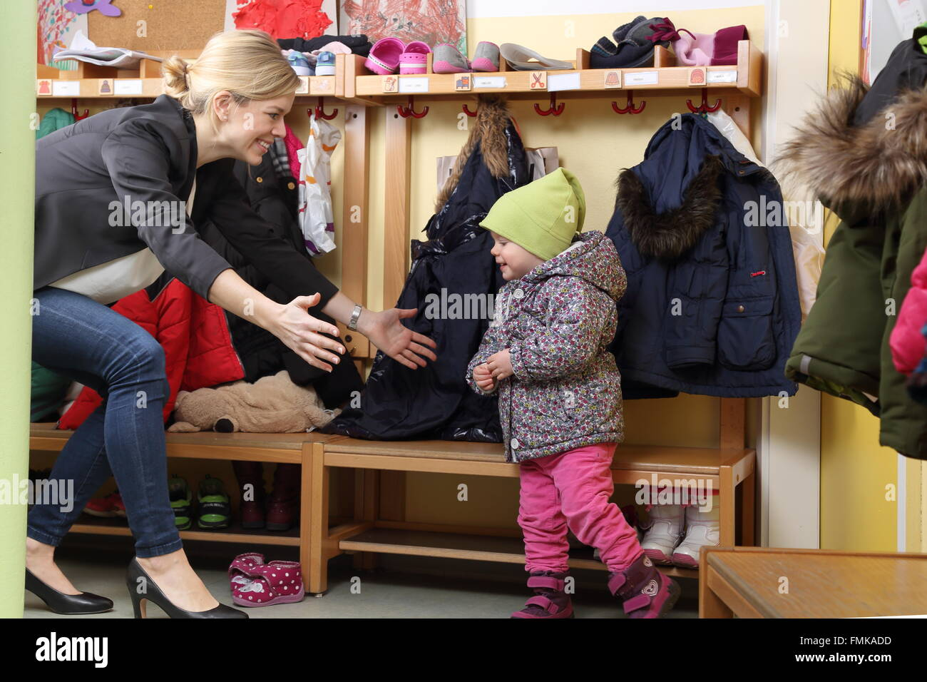 A Mother picking up her child from a Kindergarten in wardrobe - Stock Image