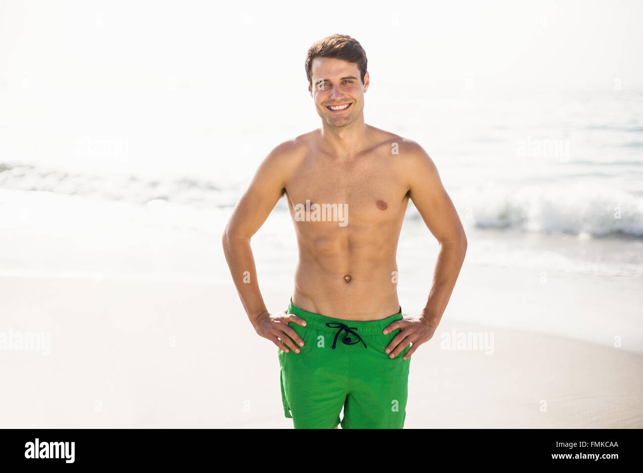 Portrait of man in swim shorts standing on beach - Stock Image