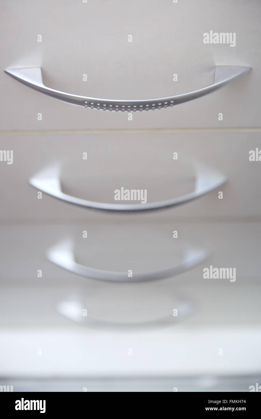 Cabinet with sliding trays and chrome handles. Close-up - Stock Image