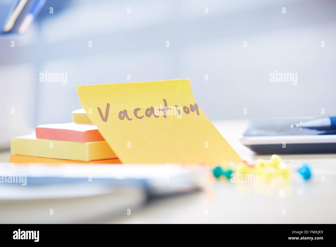 Vacation text on adhesive note at office - Stock Image
