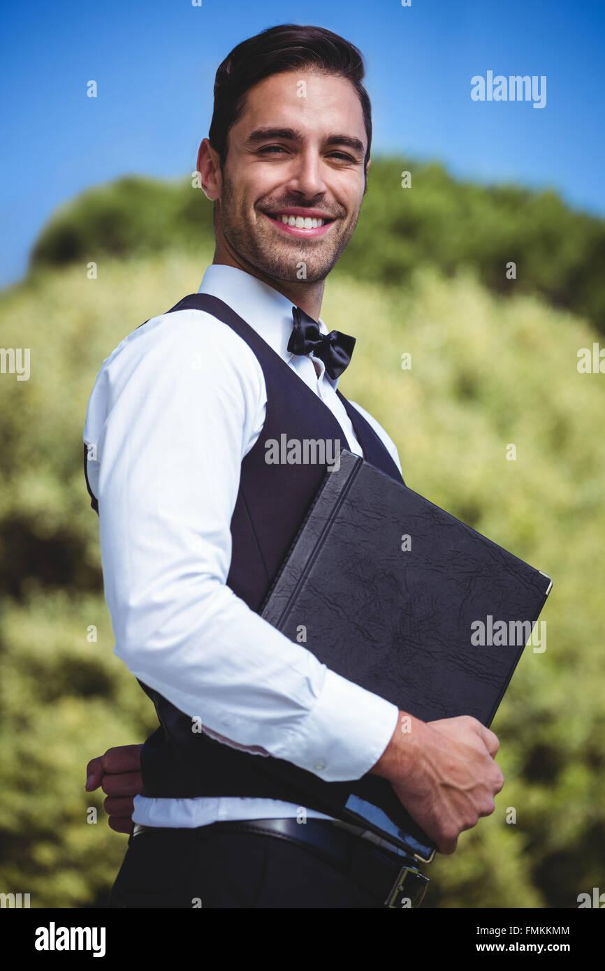 Handsome waiter holding menus - Stock Image
