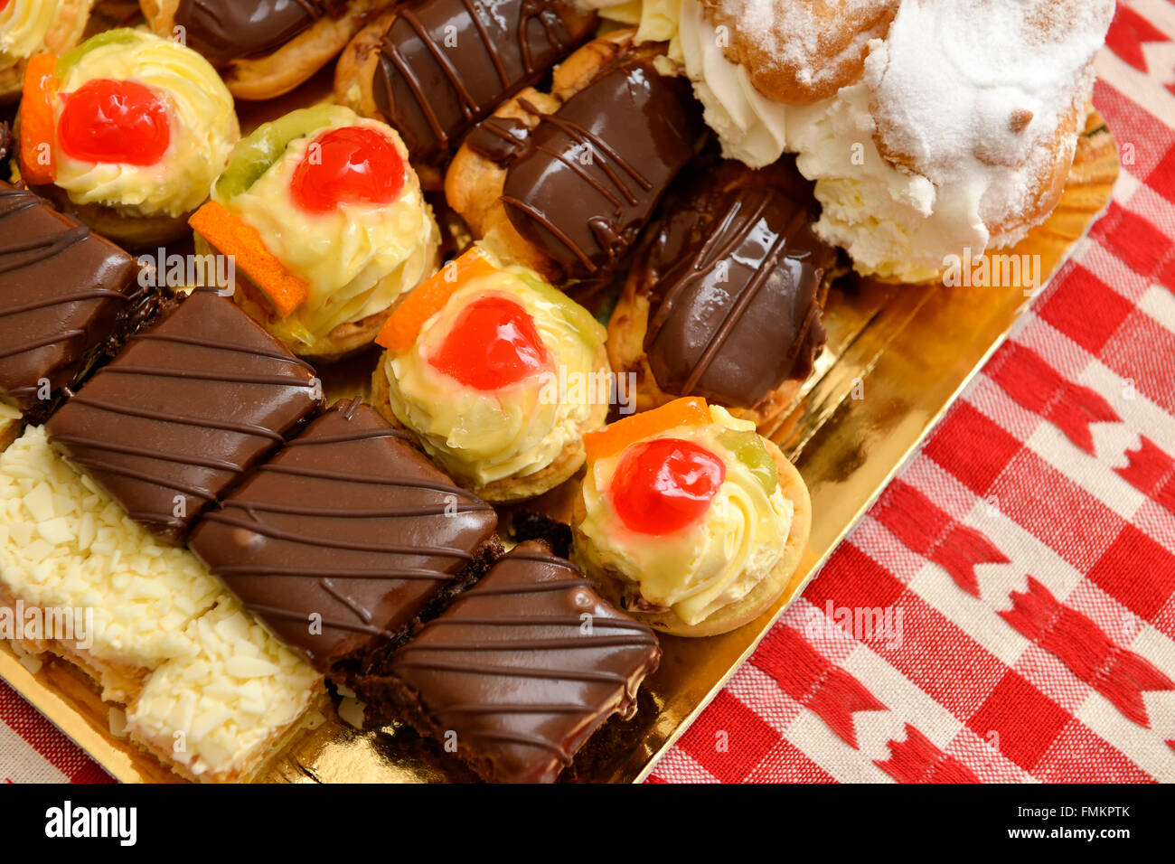 Eclair and a lot of cakes on a table - Stock Image
