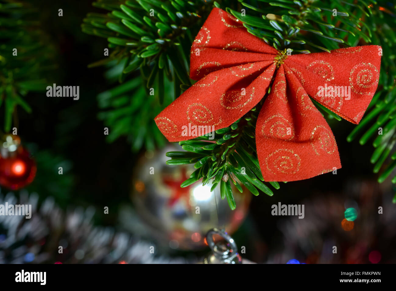 Ribbon Christmas decorations hanging in tree - Stock Image