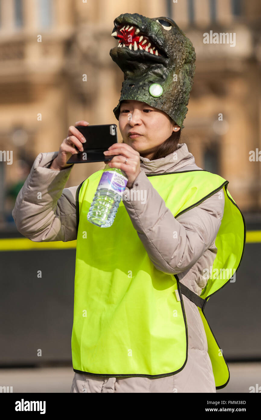 London, UK. 12 March 2016. An organiser wears a dinosaur hat at a rally held outside the Houses of Parliament in - Stock Image