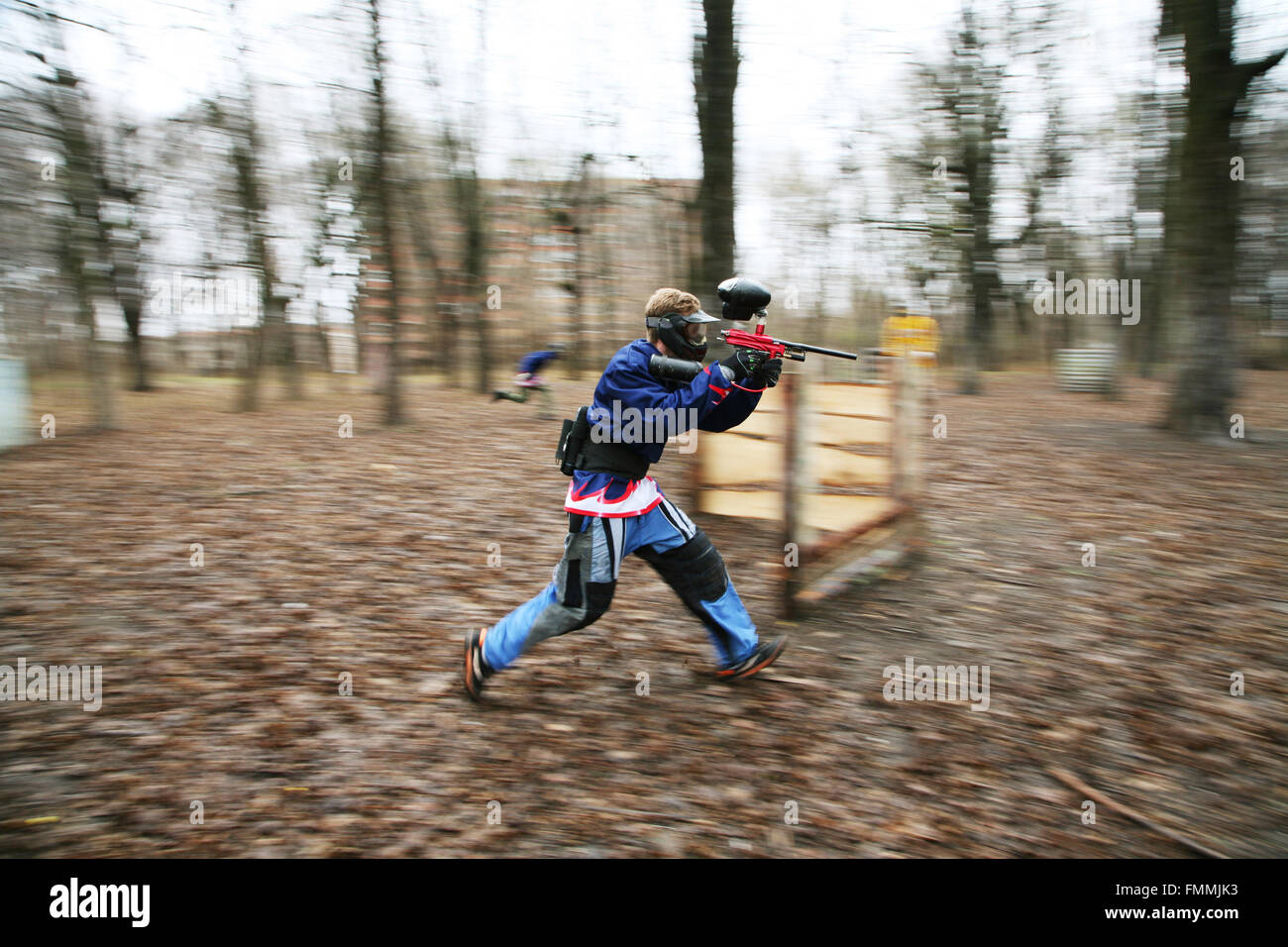 The running person with a gun for paintball Stock Photo