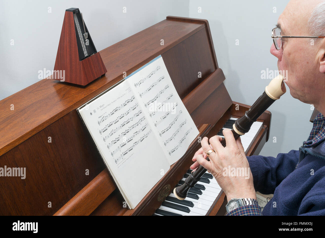 Older man playing an alto or treble recorder with a metronome to set the tempo. - Stock Image