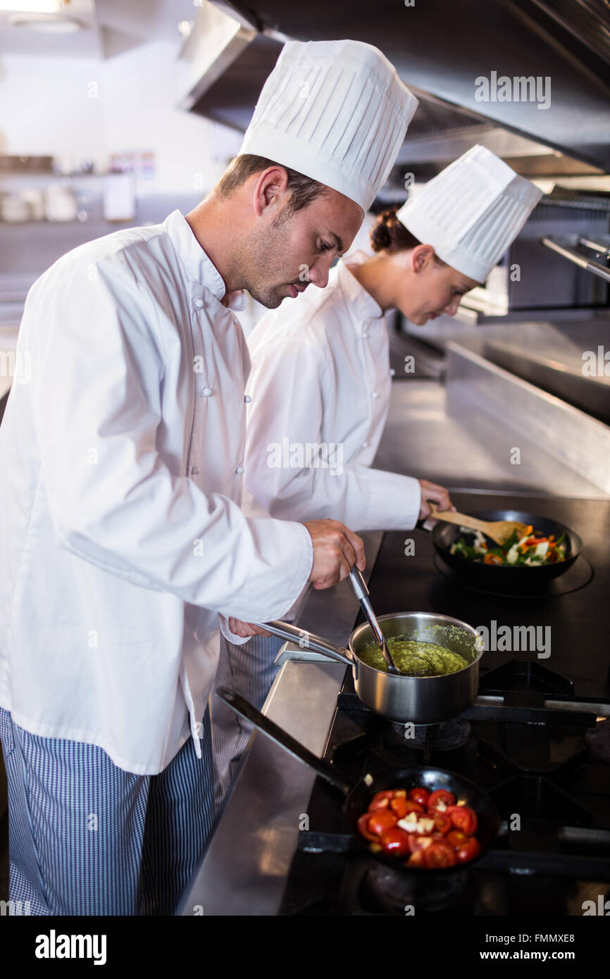 Chef preparing food in the kitche - Stock Image