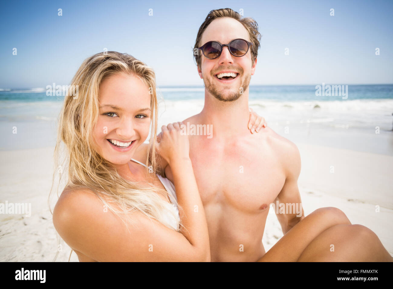 Man holding woman in his arms on the beach - Stock Image