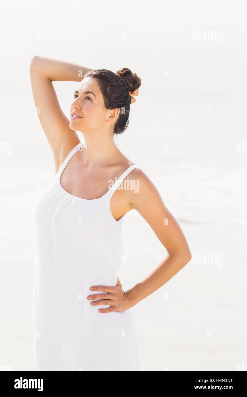 Beautiful woman in white outfit standing on the beach - Stock Image
