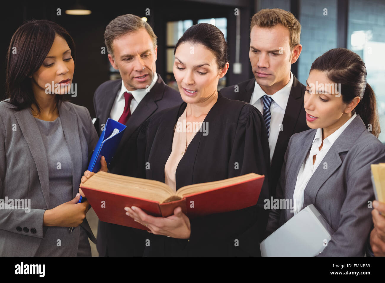 Lawyer reading a law book and interacting with businesspeople - Stock Image