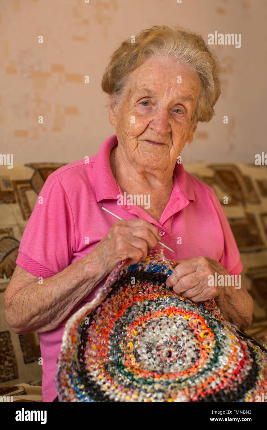 An old woman sits knitting a rug. - Stock Image