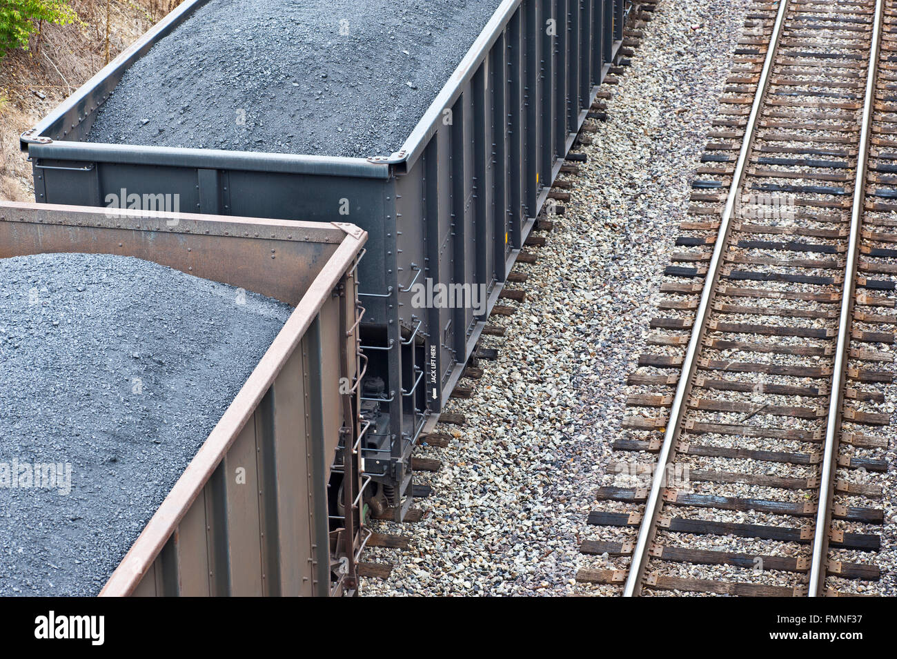Train Cars Loaded With Coal Next to More Tracks - Stock Image
