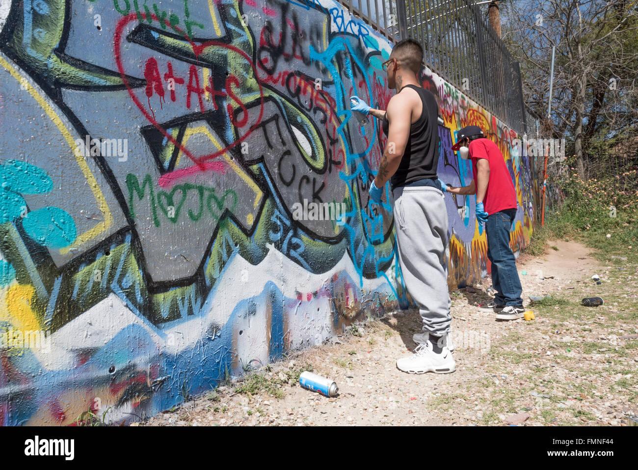 Graffiti artists spray paining on a wall at the austin graffiti park austin texas usa