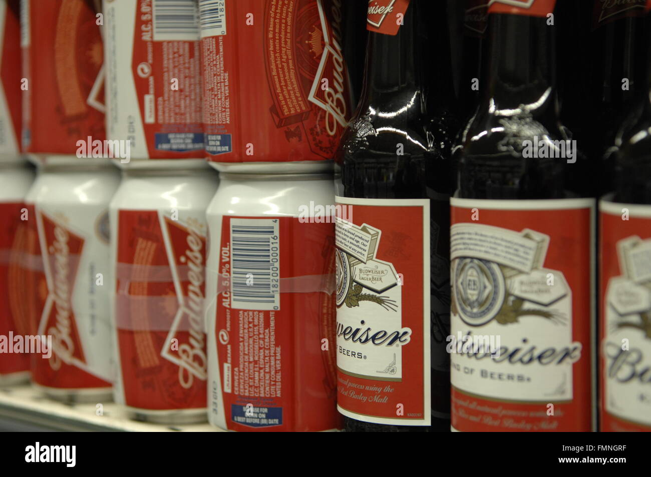 A side on image of bottles and cans of Budweiser, produced by American brewer Anheuser-Busch - Stock Image