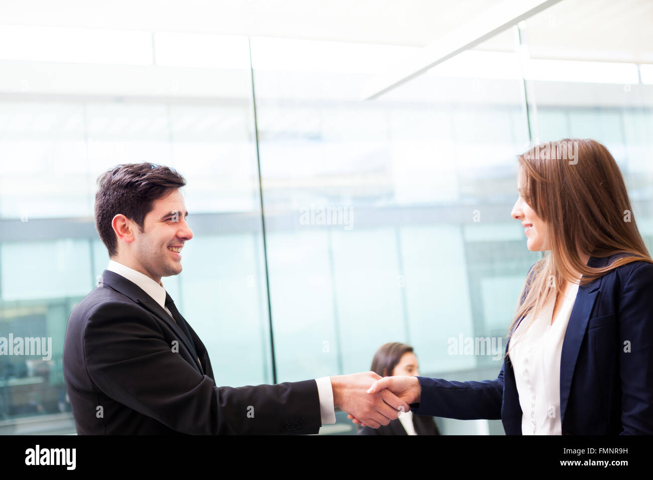 business handshake at modern office with bussiness people on stock