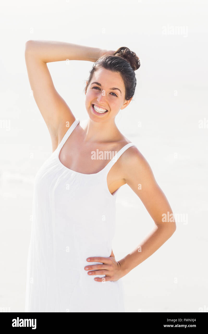 Happy woman in white outfit standing on the beach - Stock Image