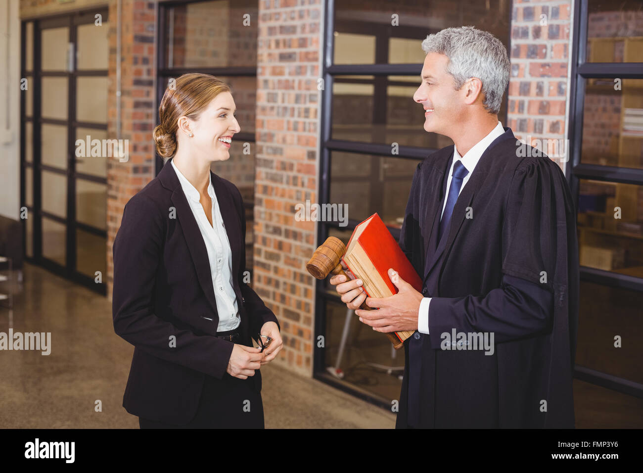 Male lawyer smiling while discussing with female colleague - Stock Image