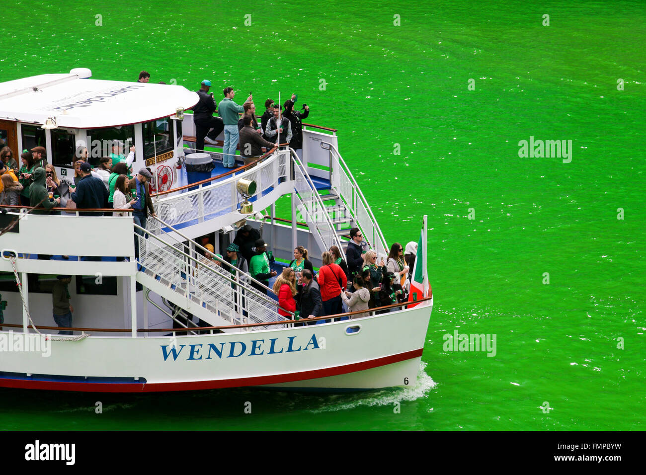 Chicago USA 12th March 2016. An excursion boat plies the Chicago River, dyed green with vegetable dye for St Patrick's - Stock Image