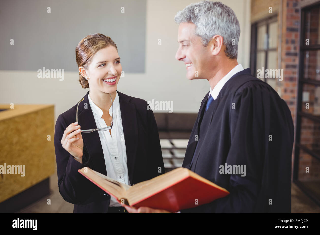 Happy Male lawyer standing by female colleague - Stock Image