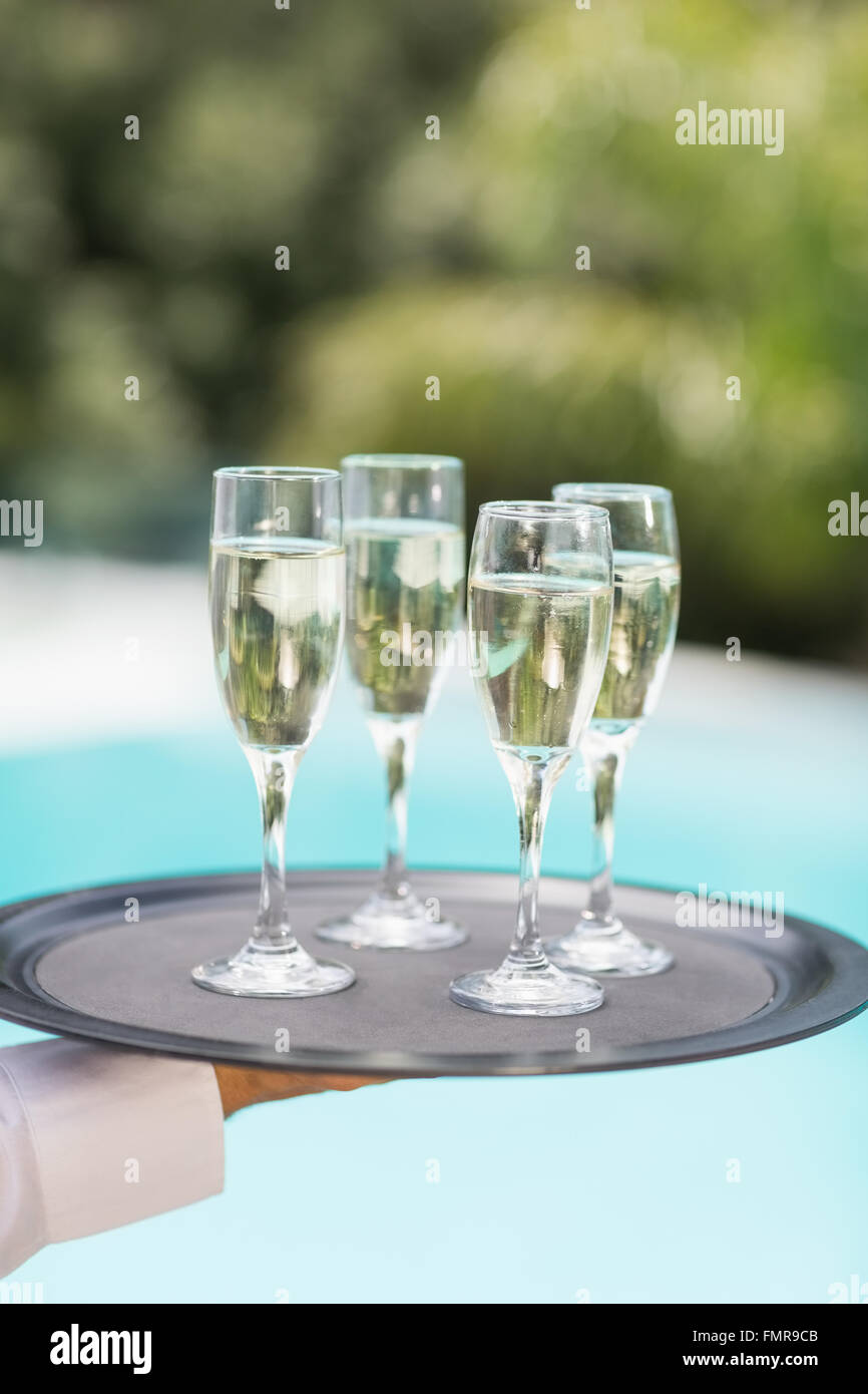 Cropped hands of waiter holding champagne flutes tray - Stock Image