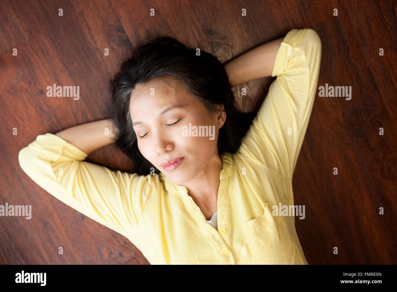 An Asian woman appears to be taking a brief nap on the floor. - Stock Image