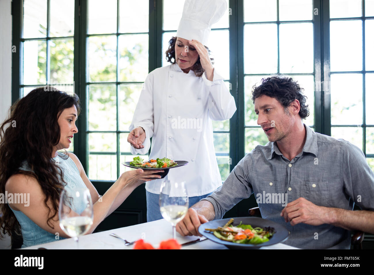 Couple complaining about the food to chef - Stock Image